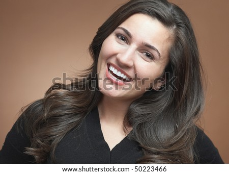 Beautiful young woman laughing on brown background - stock photo