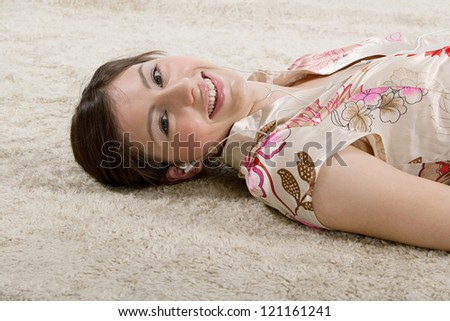 Beautiful young woman laying down on a furry carpet at home, listening to music with her headphones and smiling at the camera. - stock photo