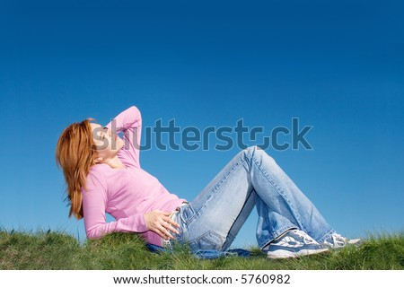 beautiful young woman laying in the grass - stock photo