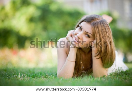 Beautiful young woman laying on a green grass in a park