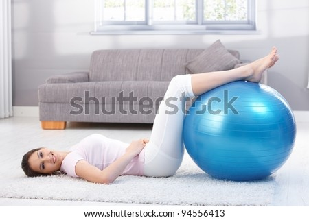 Beautiful young woman laying on floor at home, exercising on fit ball.?