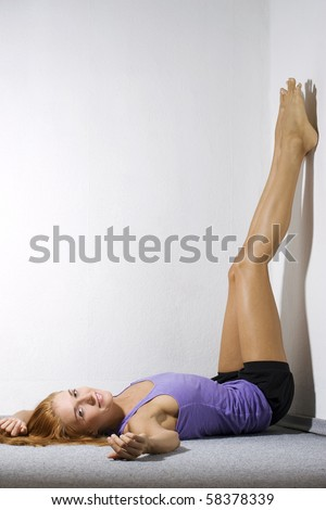 Beautiful young woman laying on the floor with her legs up