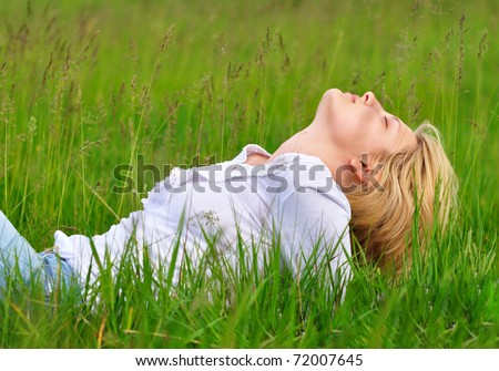 Beautiful young woman laying on the green grass and dreaming - stock photo