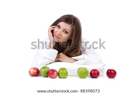 Beautiful young woman laying on white background with apples isolated