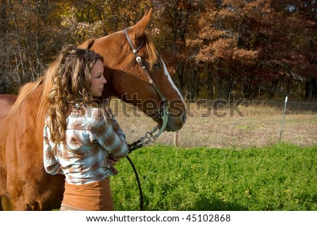 Beautiful Young Woman leading her brown horse