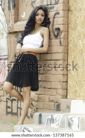 Beautiful young woman leaning against a wall with graffiti background. - stock photo