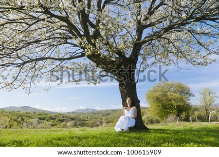 Beautiful young woman leaning on a cherry tree in bloom feeling one with Nature - stock photo