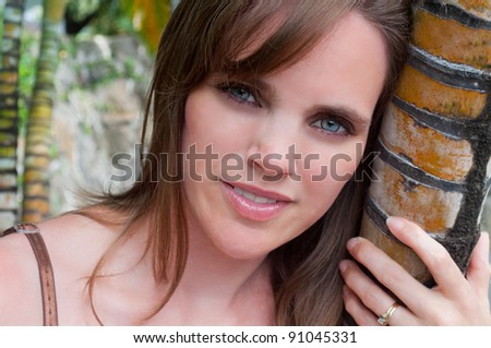 Beautiful young woman leaning on a tree - stock photo