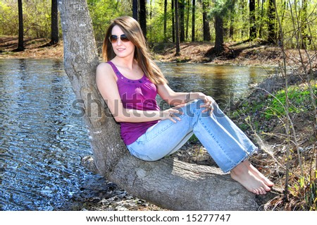 Beautiful young woman leans her back against a leaning tree besides a lake.  She is wearing jeans and purple shirt. - stock photo