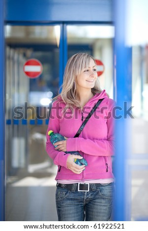 Beautiful young woman leaving a supermaket with a bottle of water - stock photo