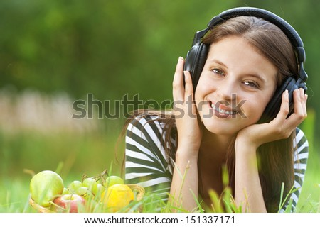 Beautiful young woman lie on grass and listening to music through headphones, against green of summer park. - stock photo