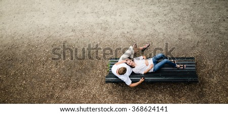Beautiful young woman lies on a bench in the park with his dead in his boyfriend lap smilling - stock photo