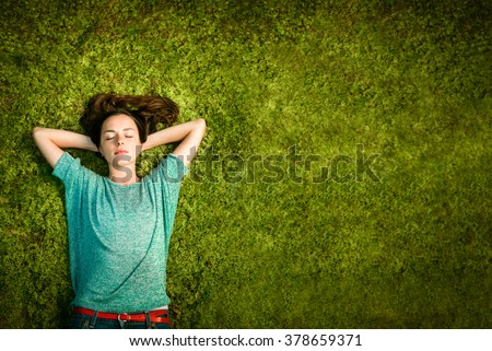beautiful young woman lies on green moss relaxing with eyes closed and hands behind his head - stock photo
