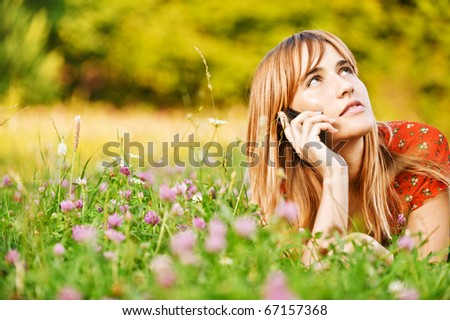 Beautiful young woman lies on green summer meadow among clover and talks by mobile phone. - stock photo