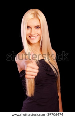 Beautiful young woman lifts thumb meaning that all remarkably, it is isolated on black background. - stock photo