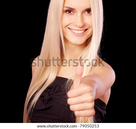 Beautiful young woman lifts thumb meaning that all remarkably, it is isolated on black background.