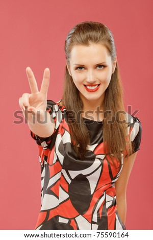 Beautiful young woman lifts two fingers the letter V in victories, on red background.