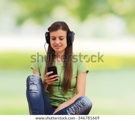 Beautiful young woman listening music and using mobile phone.