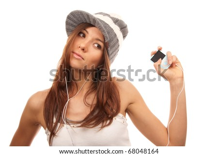 Beautiful young woman listening to dance music on mp3 player in headphones wearing hip-hop style hat and top, isolated on white background