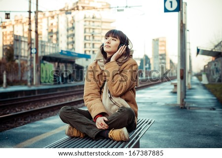 beautiful young woman listening to music headphones  in the city winter - stock photo