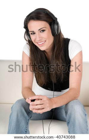 Beautiful young woman listening to music on headphones, sitting on the couch, happy and smiling, isolated on white background