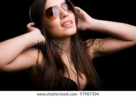 Beautiful young woman listening to music with headphones on black background
