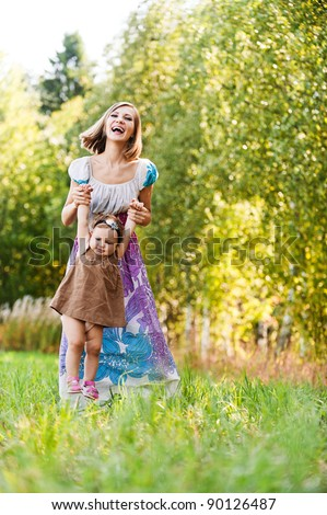 beautiful young woman long dress plays child field background summer meadow green trees - stock photo