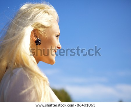 Beautiful young woman looking against the sun - stock photo