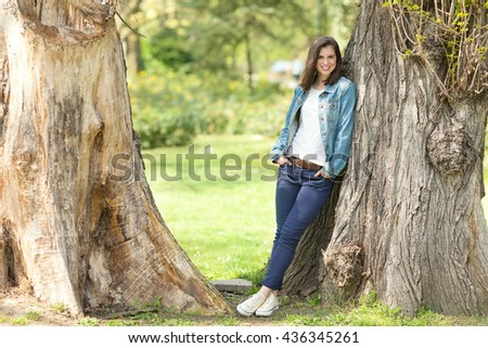 Beautiful young woman looking at camera and smiling while leaning on a tree in a park on a sunny spring day. She is standing with her hands in pockets wearing denim jacket and blue pants. Copy space - stock photo