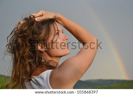 Beautiful young woman looking at the rainbow on the sky after the rain has passed and the sun has returned