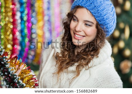 Beautiful young woman looking at tinsels in Christmas store - stock photo