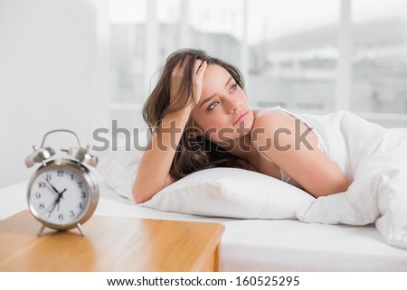 Beautiful young woman looking away while lying in bed with alarm clock on bedside table - stock photo