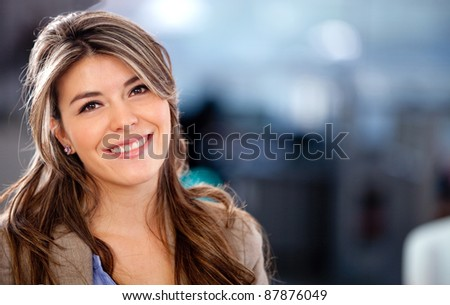 Beautiful young woman looking casual and smiling - indoors - stock photo