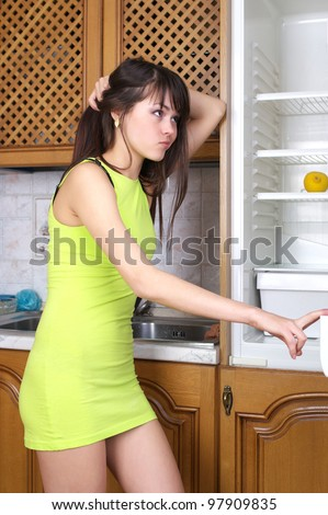 Beautiful young woman looking for something in the fridge at home - stock photo