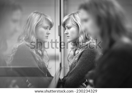 Beautiful young woman looking in the glass window, her face reflecting like in the mirror - stock photo