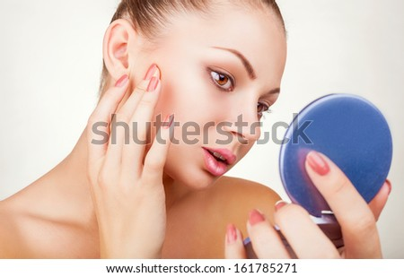 Beautiful young woman looking in the mirror on white background - stock photo