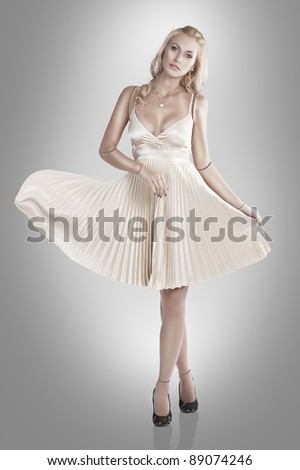 beautiful young woman looking like a porcelain doll wearing a skin colour dress - stock photo