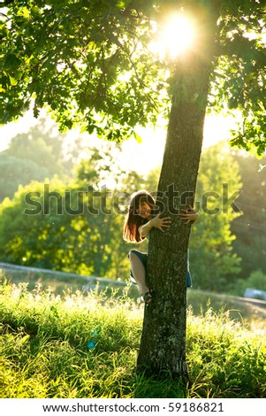 Beautiful young woman looking out of the tree - stock photo