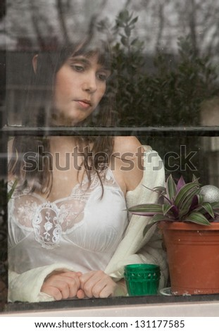 Beautiful Young Woman Looking Out Window
