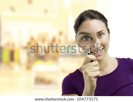 Beautiful young woman looking through a magnifying glass over a business center background - stock photo