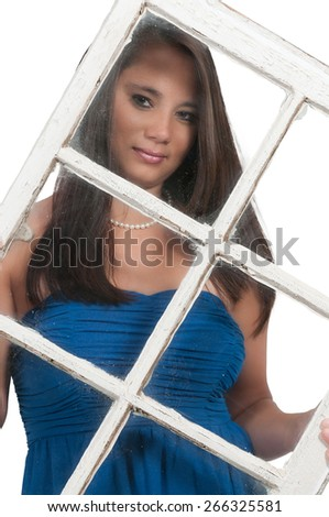 Beautiful young woman looking through an old window - stock photo