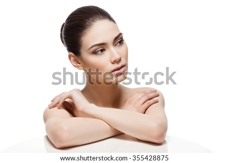 Beautiful young woman looking to the side with hands on shoulders. Isolated over white background. Copy space. - stock photo
