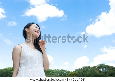 Beautiful young woman looking up at the sky - stock photo