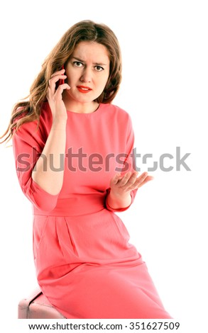 Beautiful young woman  looks frustrated while talking on the phone. Isolated on white background. - stock photo