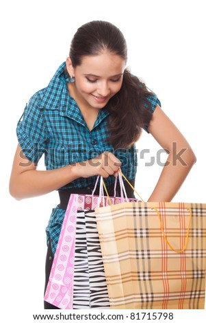 Beautiful young woman looks in the bag for shopping on white background - stock photo