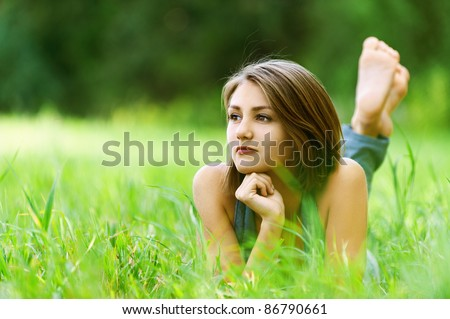 beautiful young woman lying clearing feet up leaning hands dreaming - stock photo
