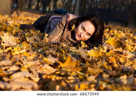 Beautiful young woman lying down in autumn leaves in park