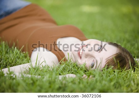 Beautiful young woman lying down of grass - stock photo