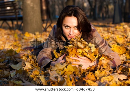 Beautiful young woman lying down with the heap of maple leaves in park
