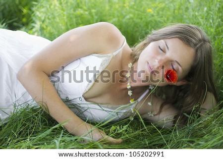 Beautiful young woman lying in a meadow with eyes closed, holding a flower - stock photo
